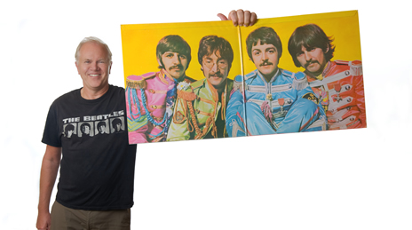 Steve holding a poster of The Beatles